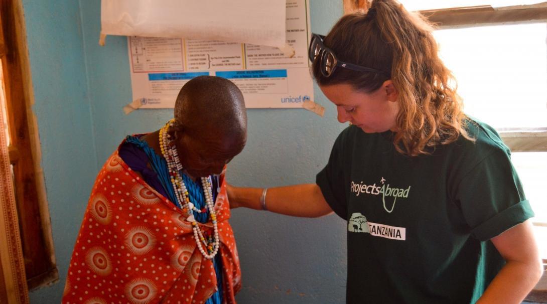 Interna ayuda a pesar a mujer masái en una clínica durante sus prácticas de enfermería en Tanzania.